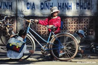Schoolgirls repairing their bicycle