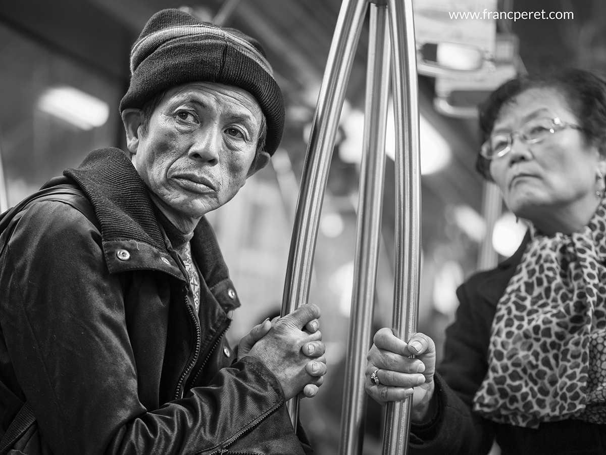 This B&W portrait in subway emphasize people connection by holding the same aluminium pole.