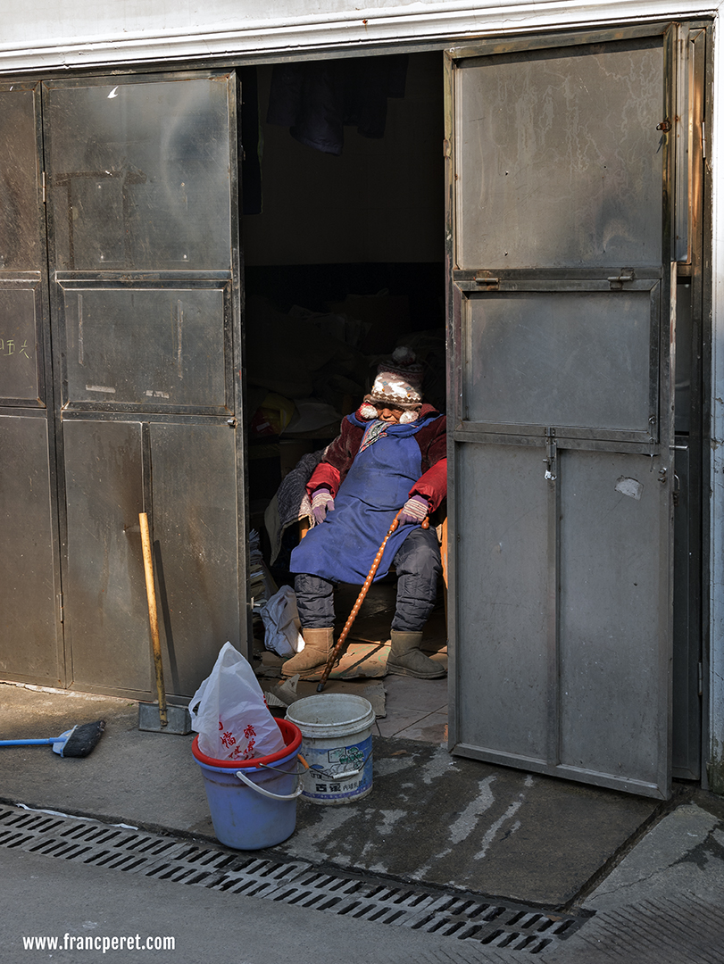This picture of the old lady sleeping in a garbage container is working very well in color too as  red and blue are the only two main dominant colors related to the lady's occupation (tools and apron). The color in the center of the image reinforce the cold and lifeless feel of her surrounding.