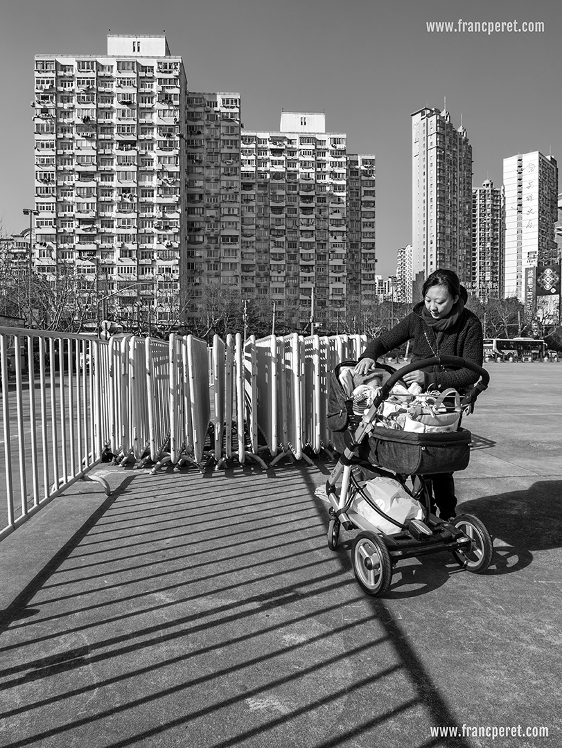 On the B&W shot, human presence becomes more unique and important as the rest of the image is filled with common element, rectilinear structures which are not differentiated by their different colors anymore. It is like pure life (a mother with her baby) versus a dehumanized environment.