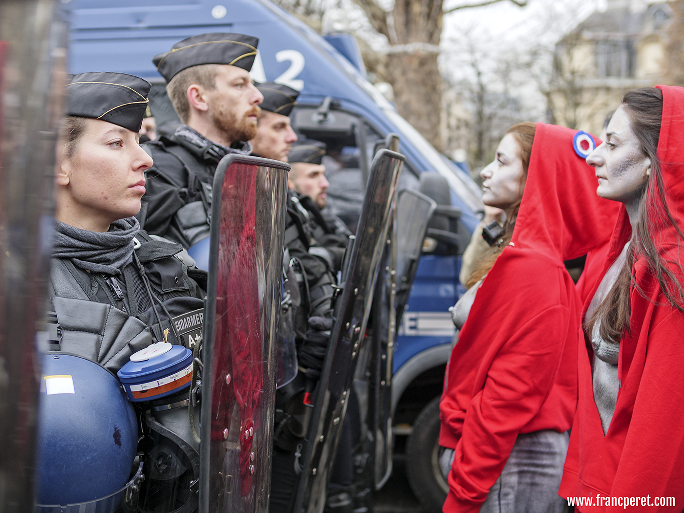 Femen facing Gendarme who smartly set a woman in front of them.